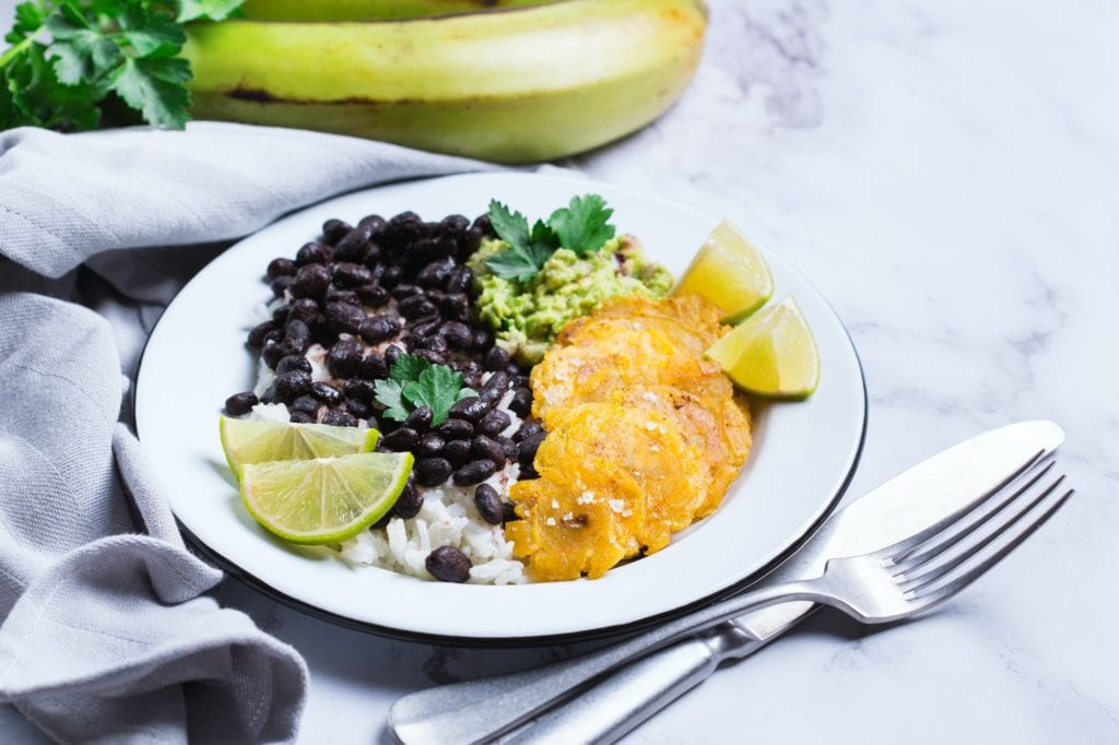 Rice with black beans, fried tostones, plantains, guacamole sauce