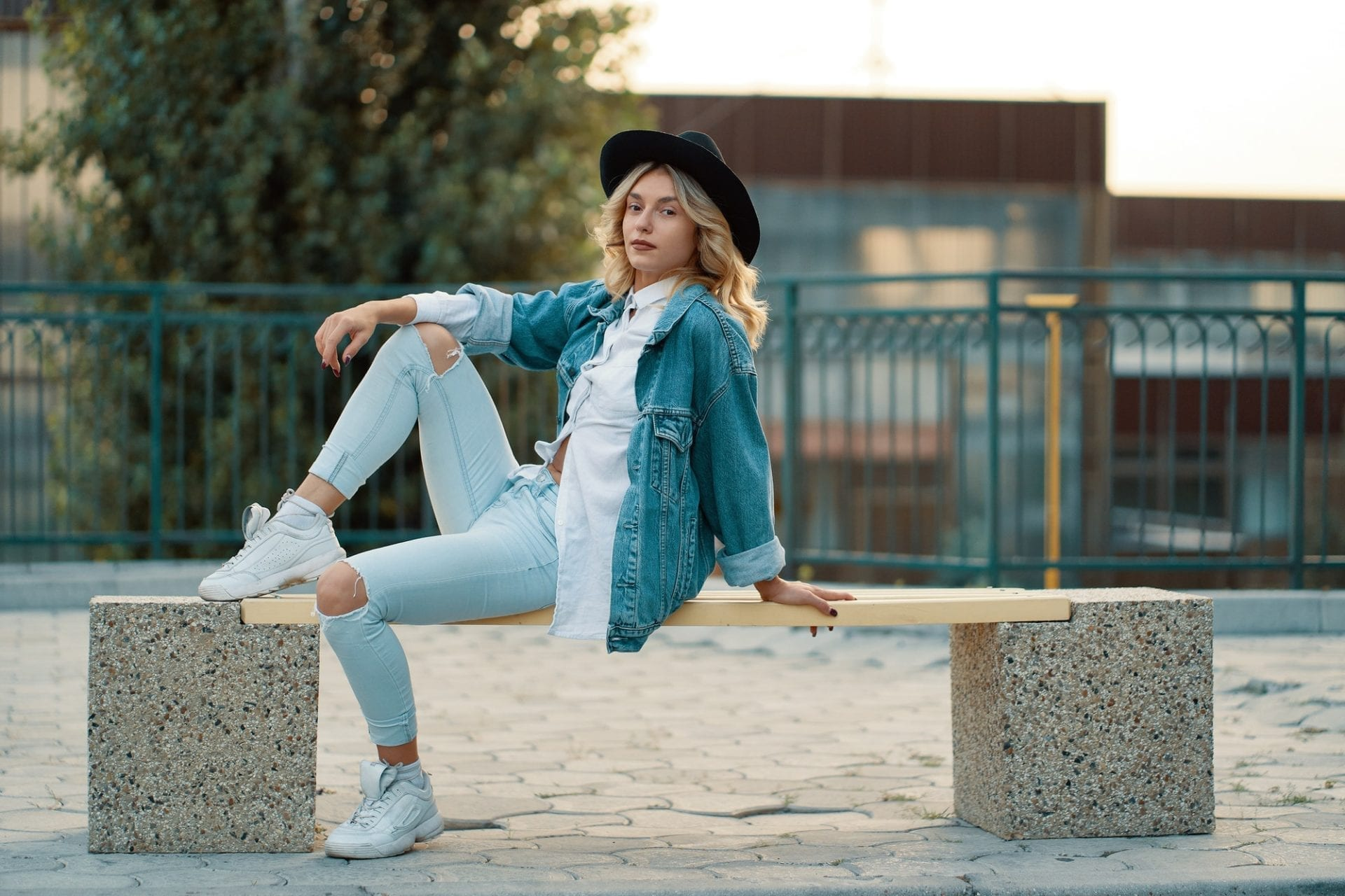 A modern, stylish girl posing while sitting on a minimal city be