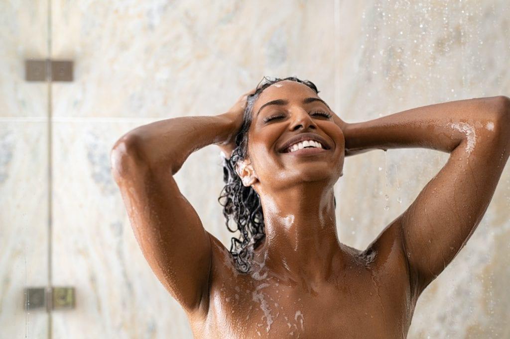 African woman washing hair under shower
