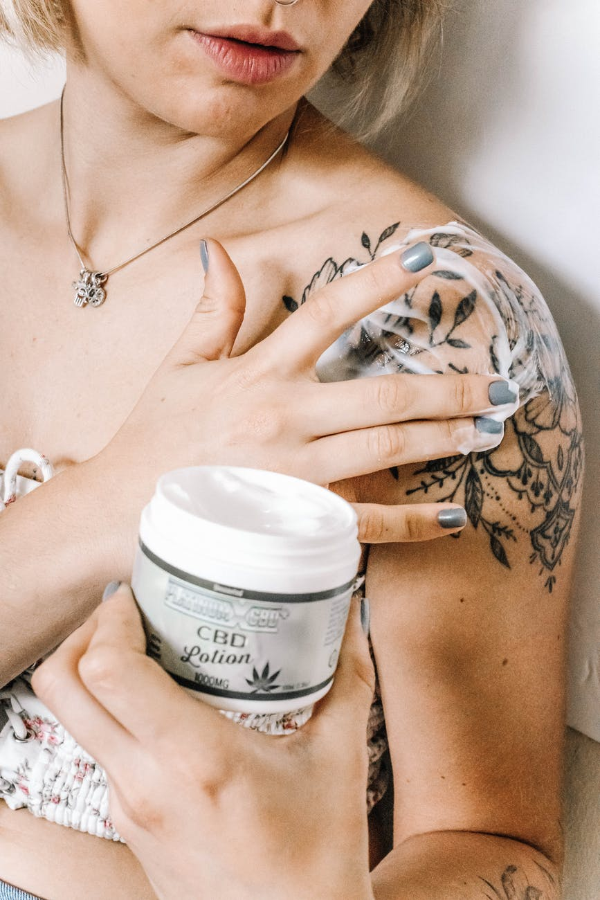 woman putting cbd lotion on skin
