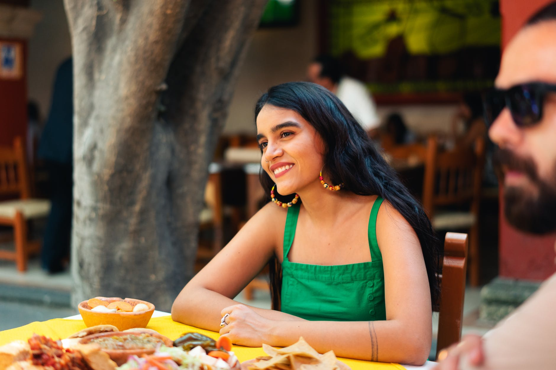 woman in green tank top eating mexican food