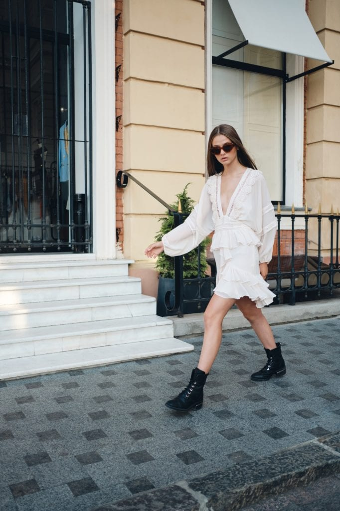 Young model in sunglasses, white dress and boots thoughtfully looking in camera walking on street