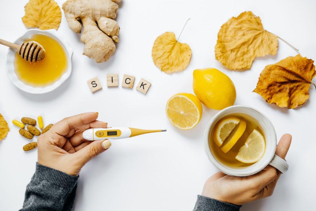 Female hands with tea, Wooden word sick, lemon