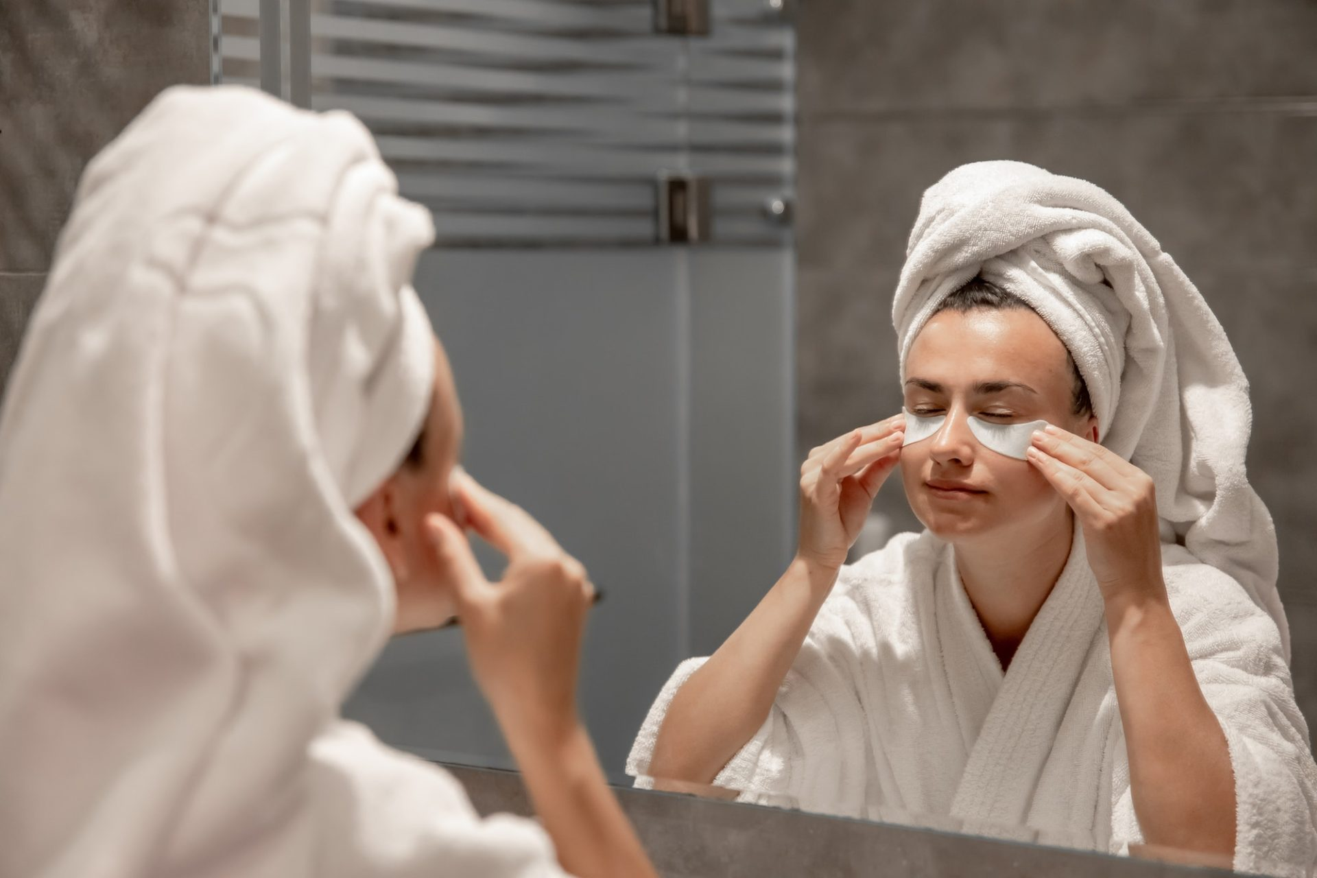 A young woman in a robe and with a towel on her head is putting patches under her eyes.