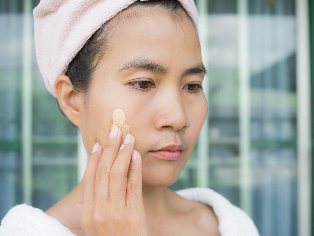 Asian woman apply sunscreen