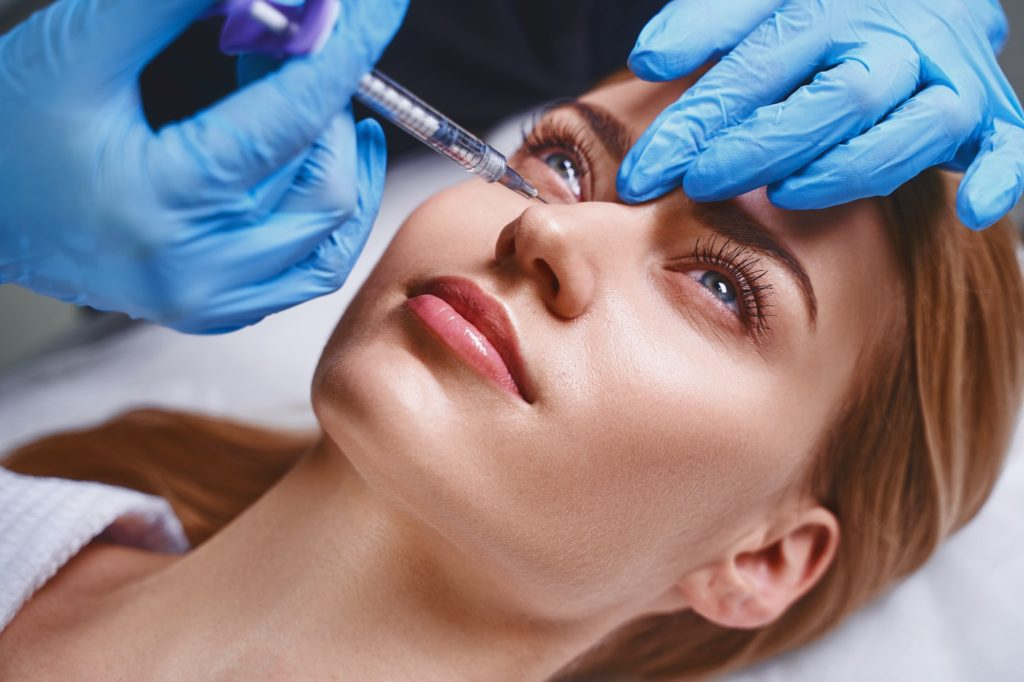 Female is trying antiage fillers stock photo