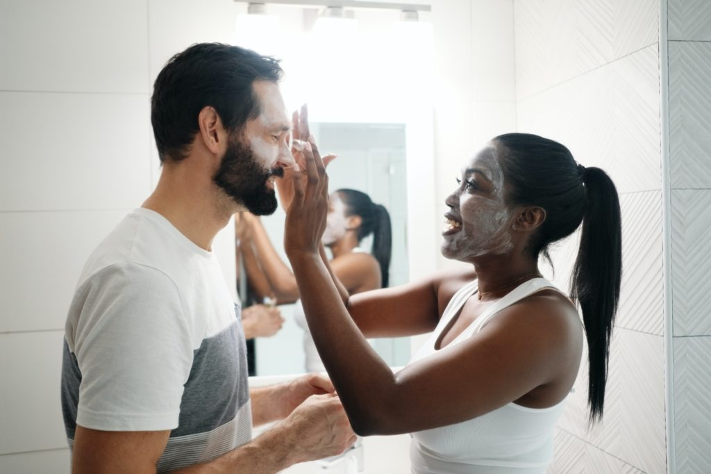 Woman Applying Beauty Mask And Skin Cleanser To Man