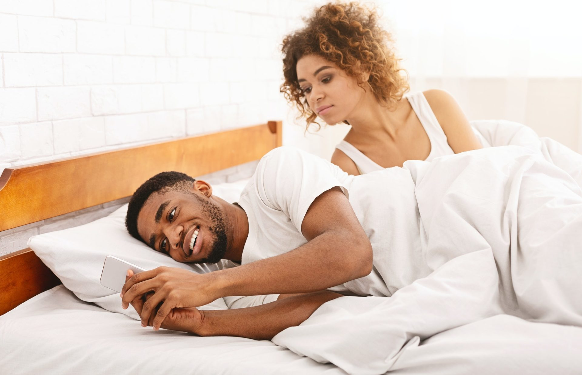 Cheating african man chatting with mistriss in family bed
