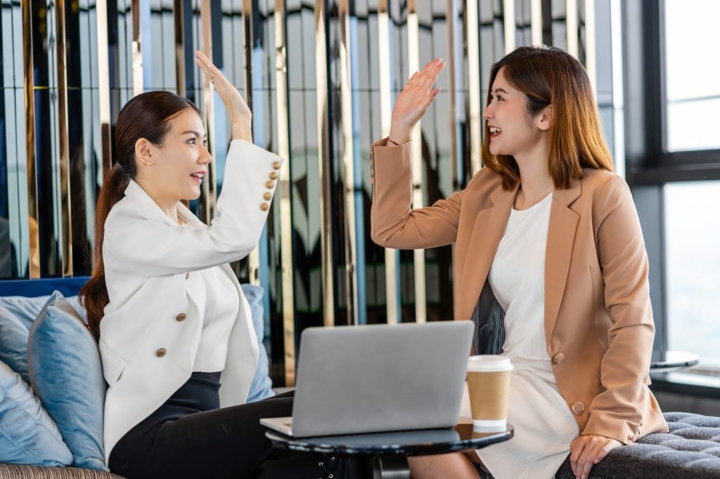 Two asian businesswomen hapiness celebrating together when checking success goal