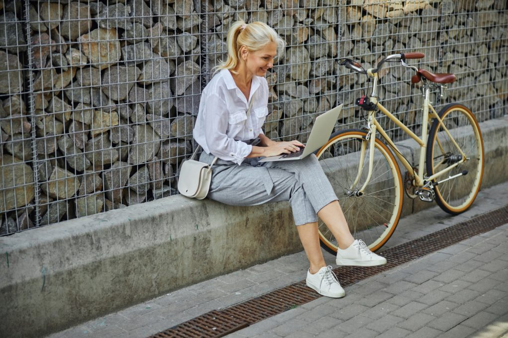 Fashionable happy female in business casual clothes sitting in front of stone wall with laptop