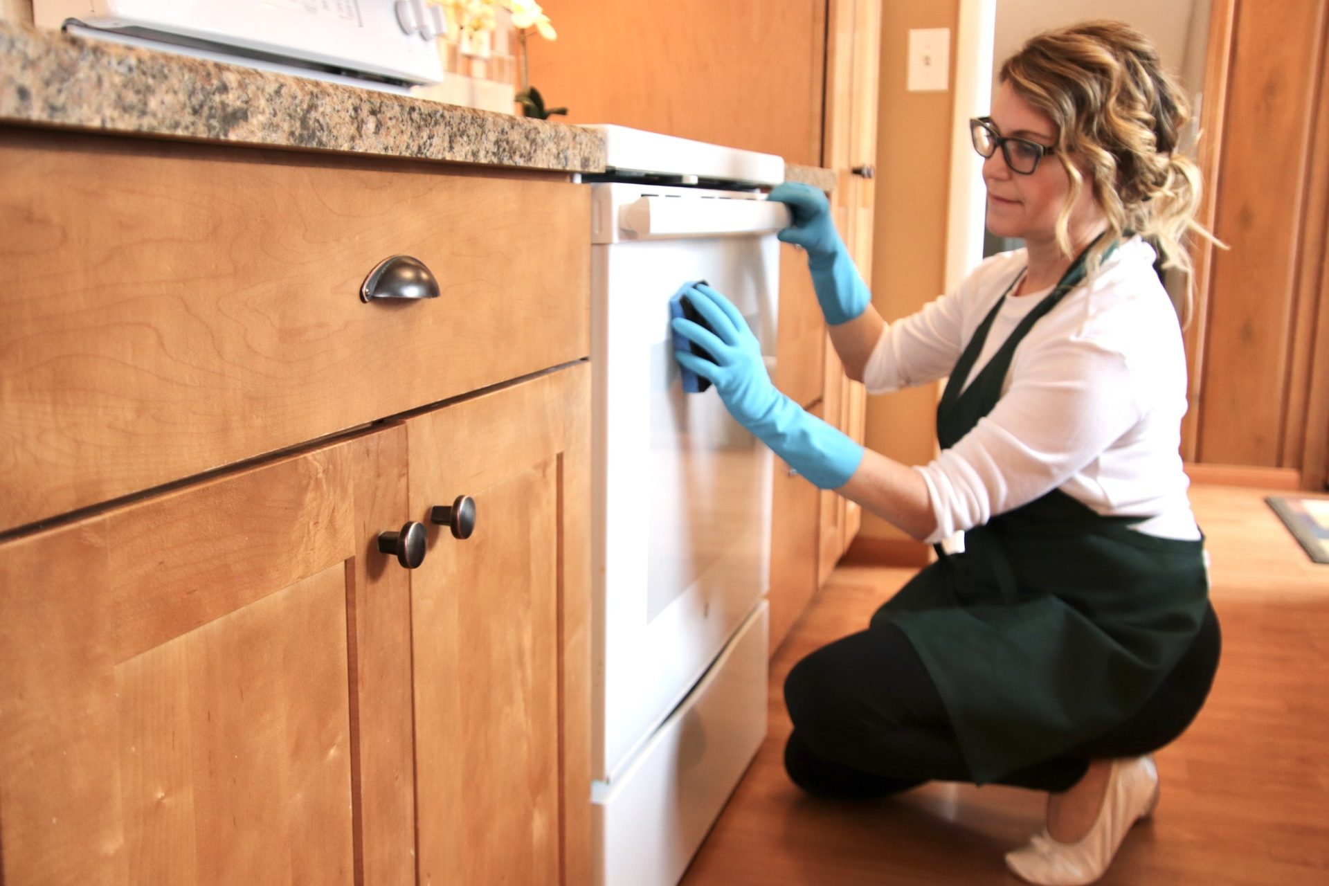Woman cleaning outside of oven