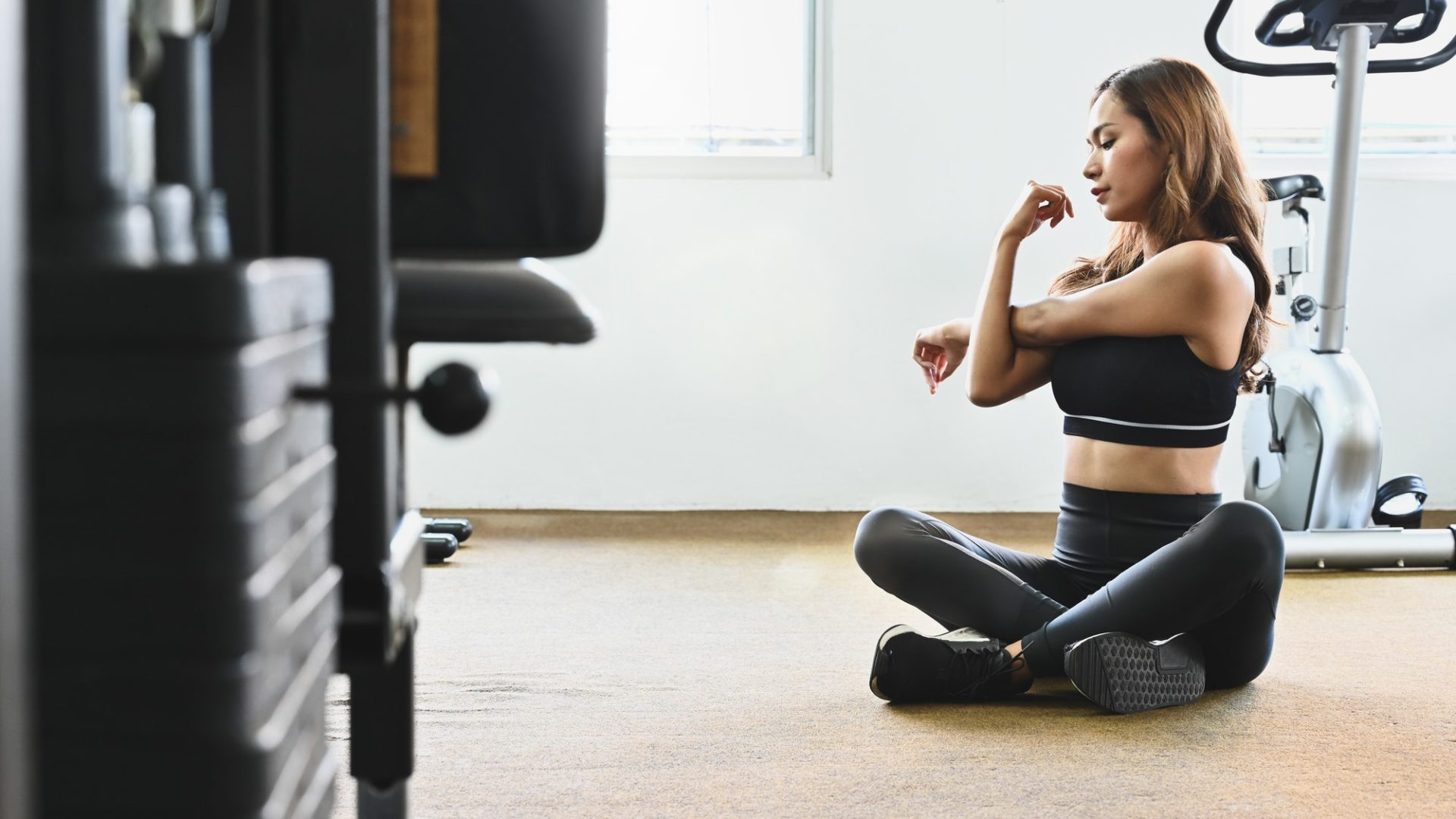 Young Woman stretching before a gym workout.