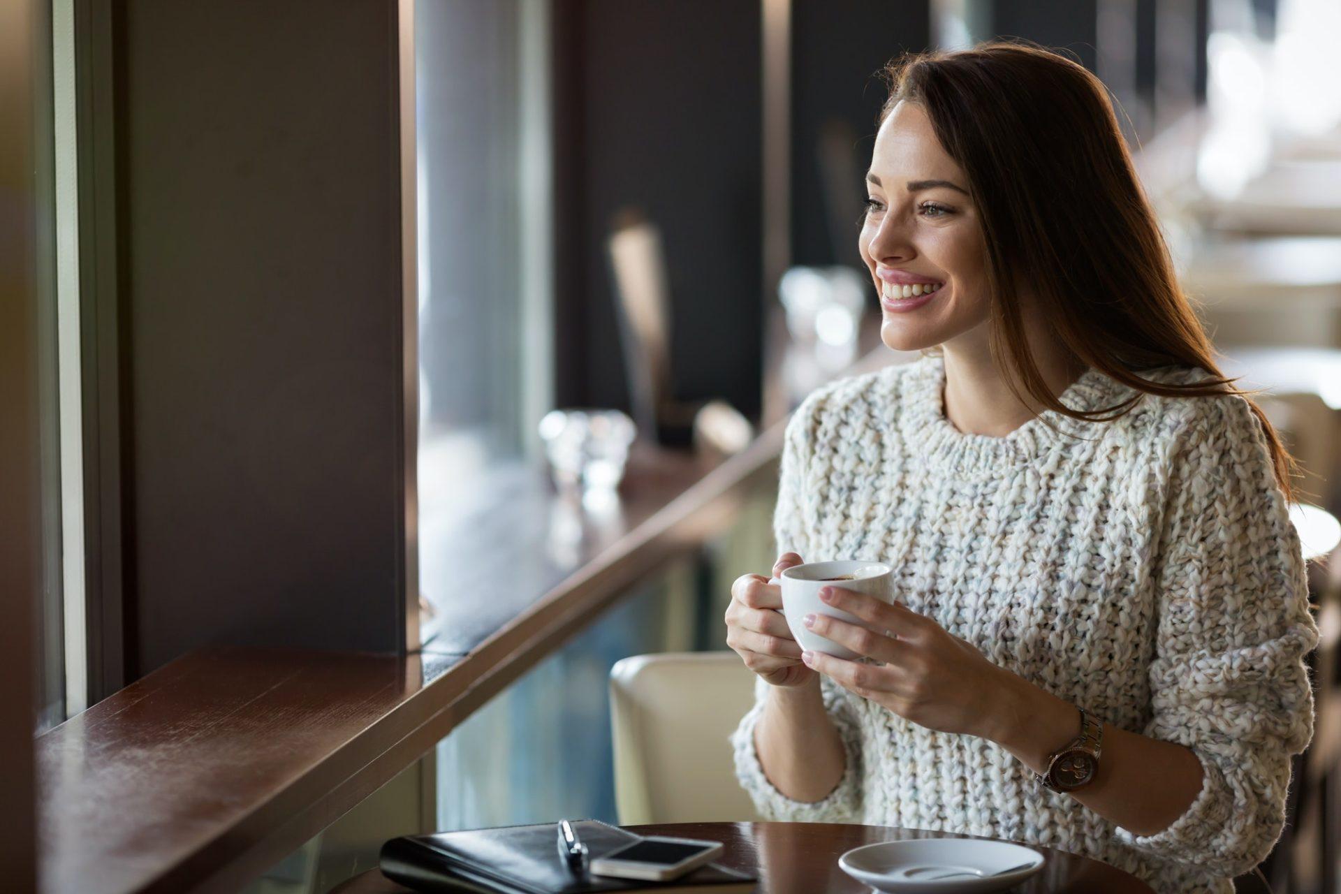 Beautiful woman drinking coffee in restaurant alone