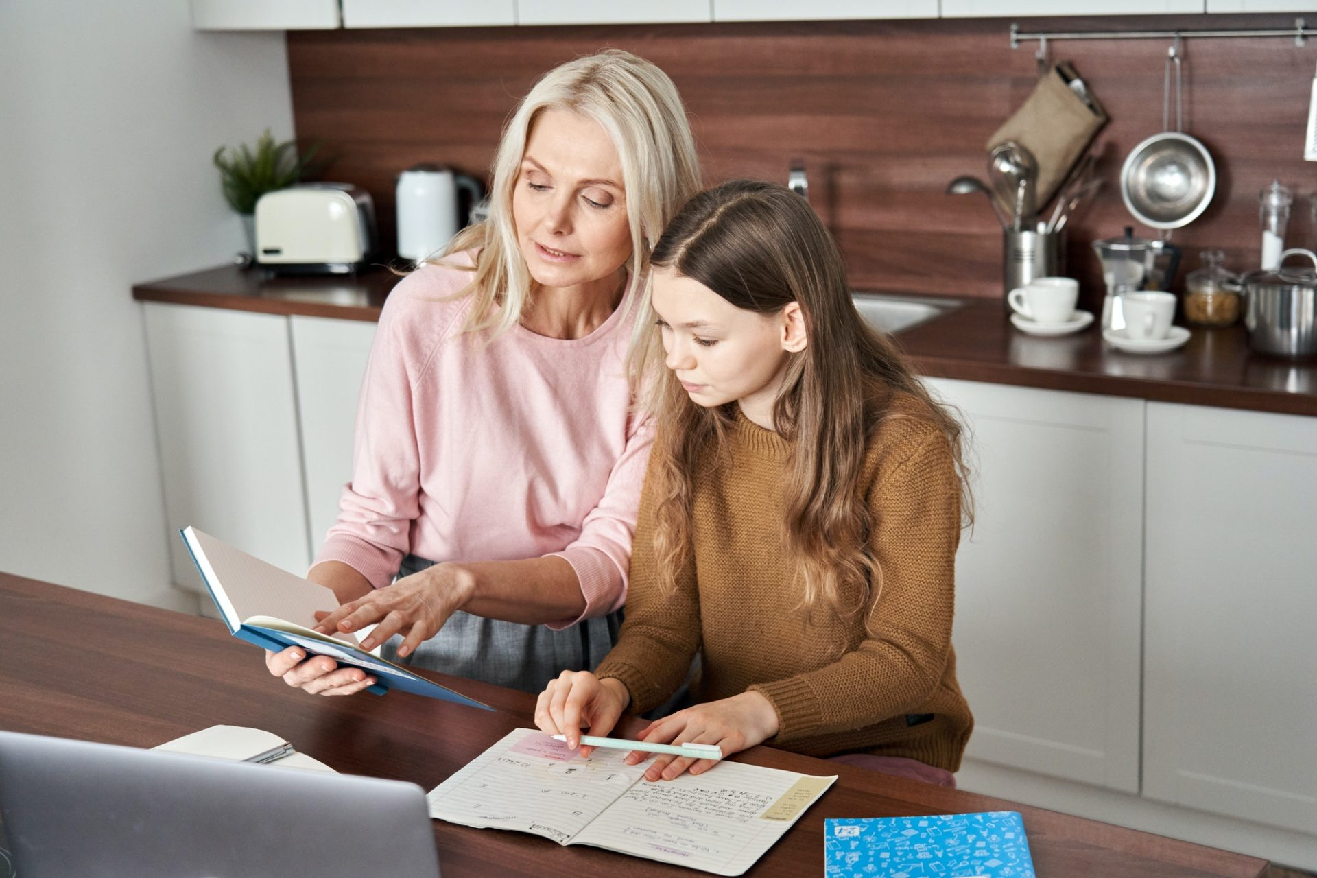 Teen child daughter studying at home in kitchen with mom.